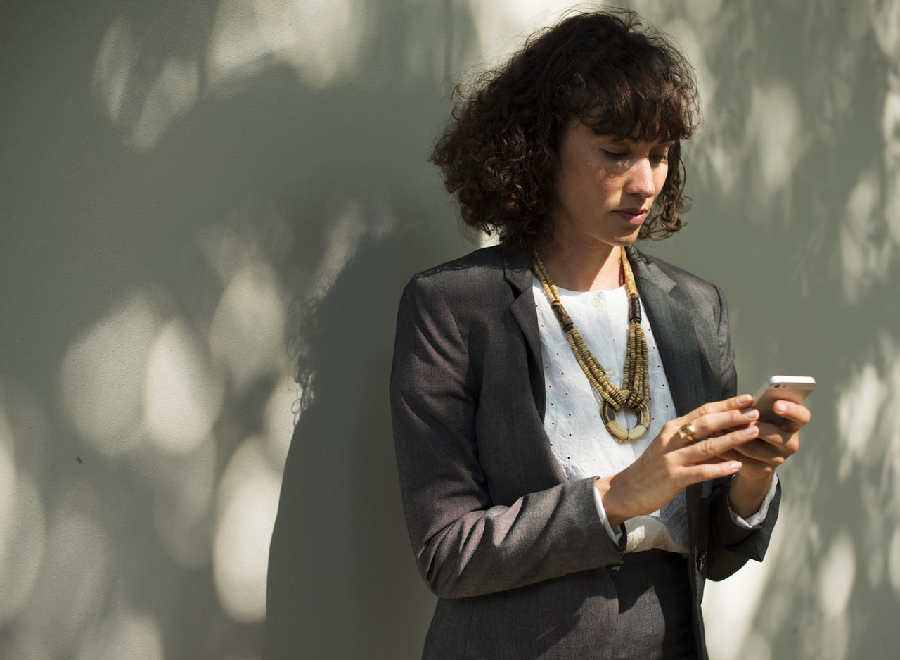 https://www.pexels.com/photo/woman-in-black-blazer-holding-a-smartphone-while-standing-near-wall-586336/